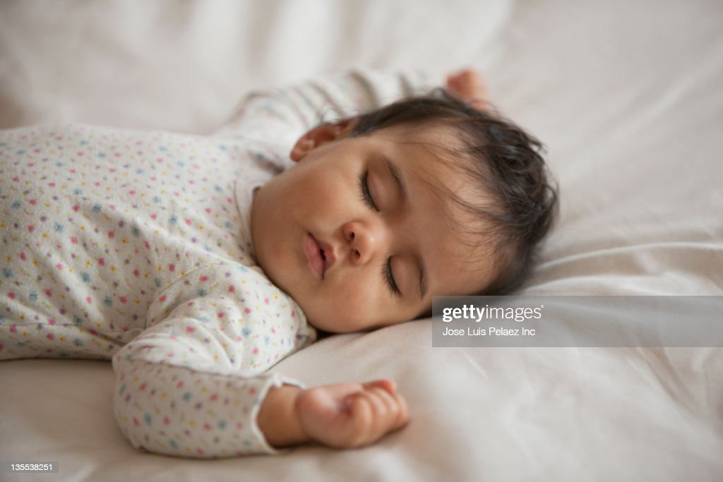 Mixed race baby girl sleeping on bed : Stock Photo