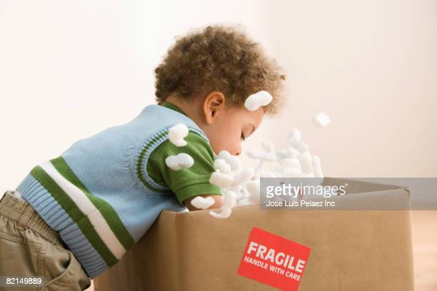 Mixed Race baby opening box with packing material