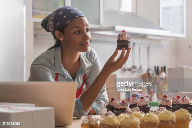 mixed race baker admiring cupcake in commercial kitchen - entrepreneur stock pictures, royalty-free photos & images