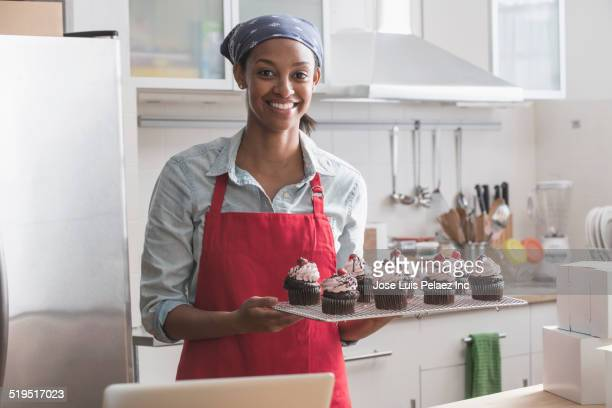 Mixed race baker holding tray of cupcakes in commercial kitchen