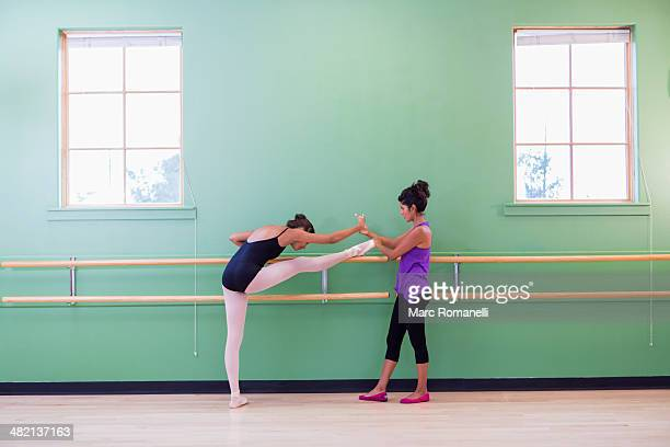 Mixed race ballerina practicing with teacher at barre