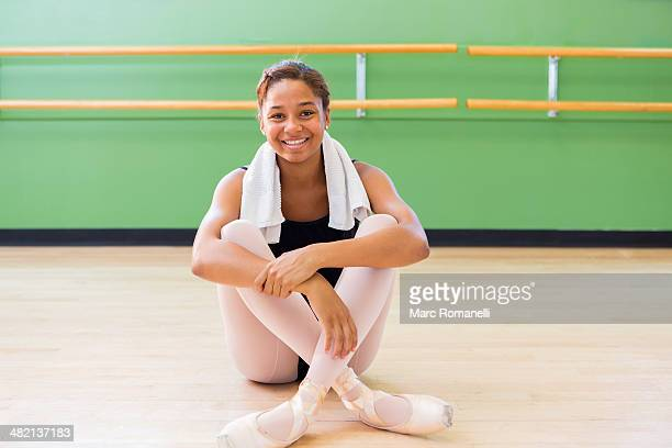Mixed race ballerina smiling in studio