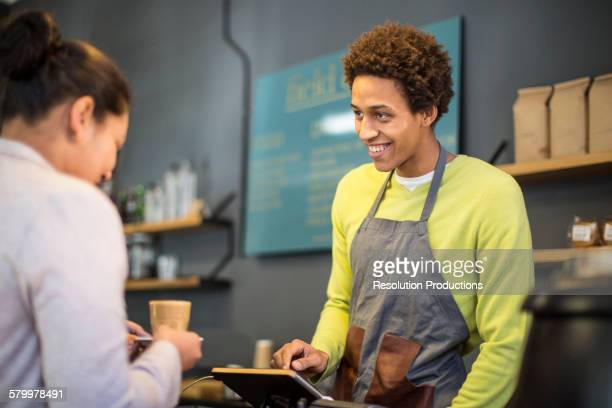 Mixed race barista assisting customer in coffee shop