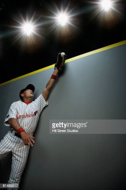 mixed race baseball player catching ball - 野球のユニフォーム ストックフォトと画像