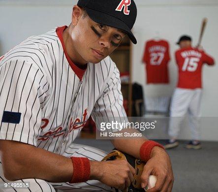 African Baseball Player Holding Bat In Locker Room Stock Photo