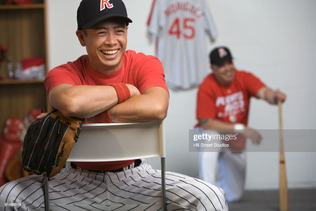 Mixed Race Baseball Player Laughing In Locker Room Stock Photo