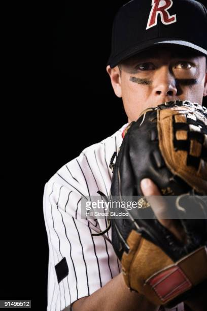Mixed race baseball player pitching