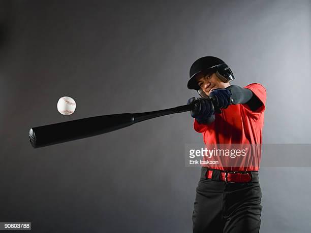 Mixed race baseball player swinging bat