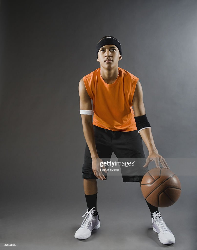Mixed race basketball player dribbling basketball : Stock Photo