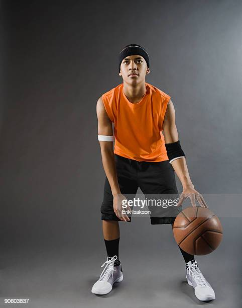 Mixed race basketball player dribbling basketball