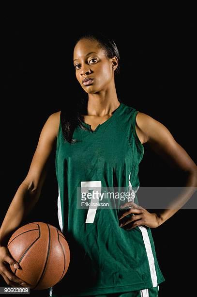 mixed race basketball player holding basketball - スポーツユニフォーム ストックフォトと画像