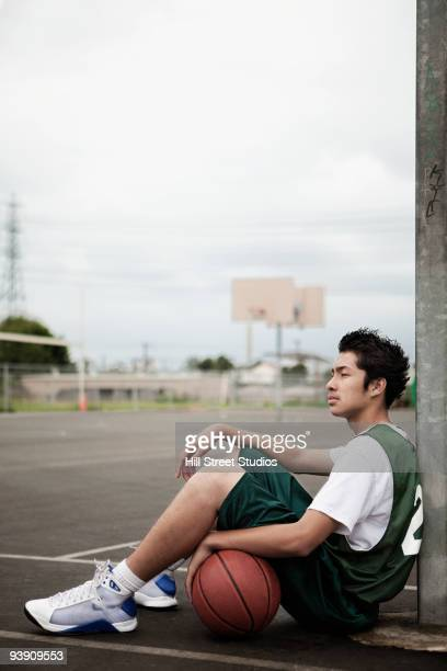 mixed race basketball player sitting with ball under basket - スポーツ用語 ストックフォトと画像