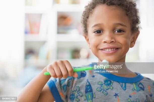 Mixed race boy brushing his teeth