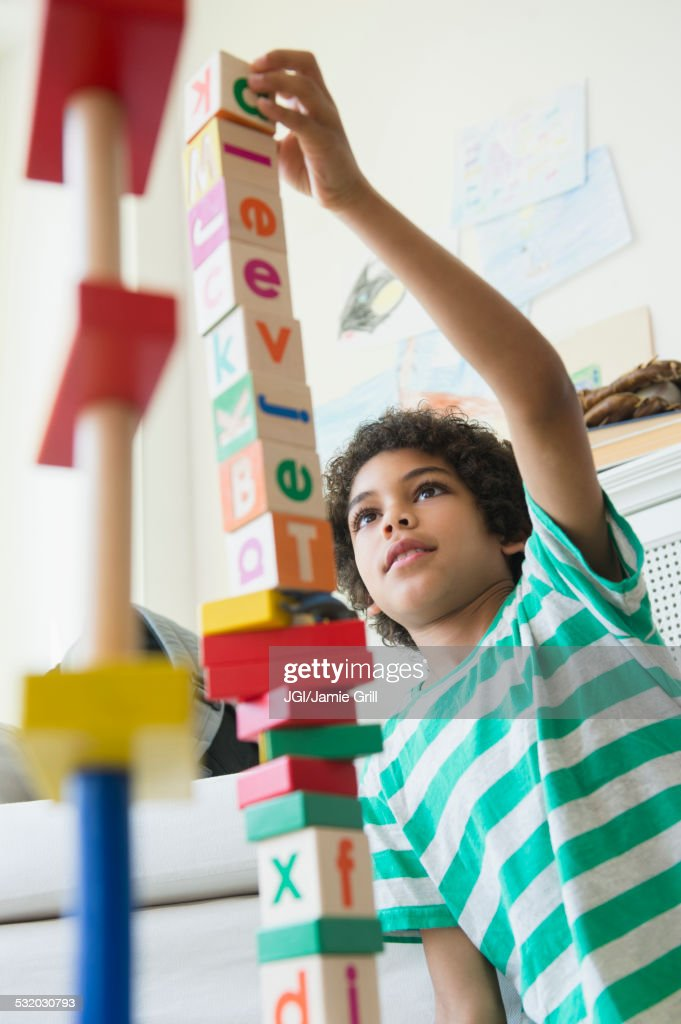 Mixed race boy building wooden block tower in living room : Stock Photo