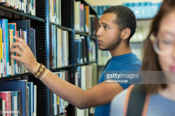 Mixed Race boy choosing book in library