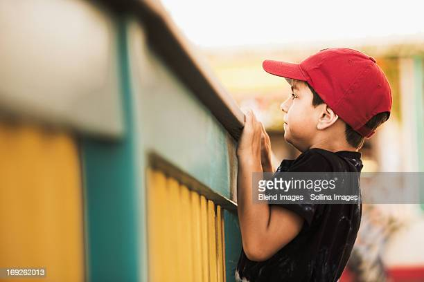 Mixed race boy climbing on banister
