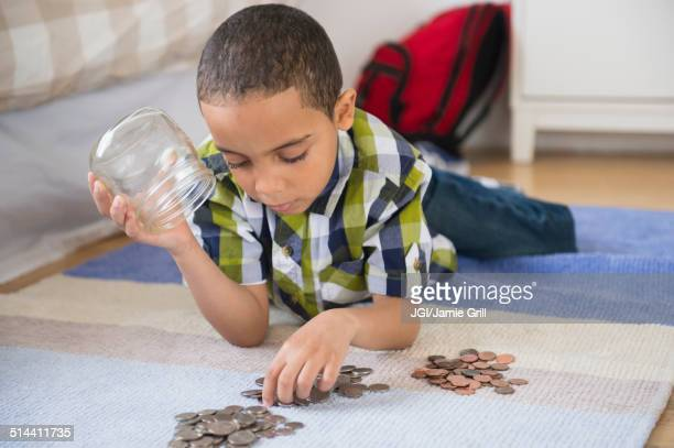 Mixed race boy counting change on floor