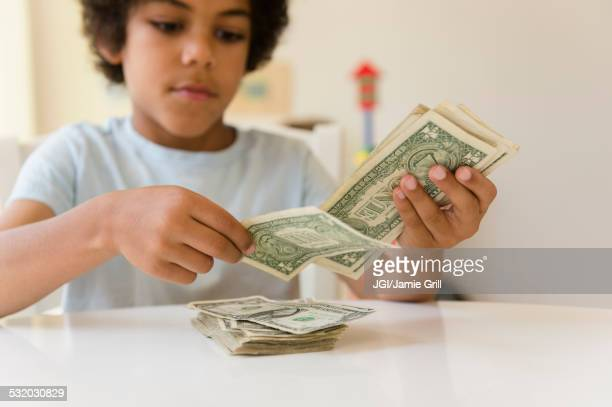 Mixed race boy counting money