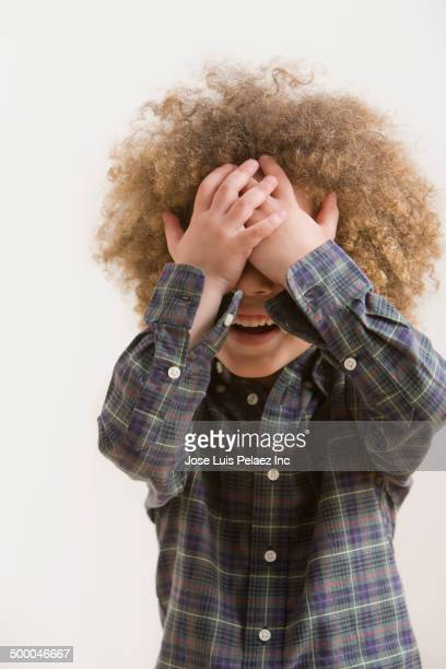 Mixed race boy covering his face