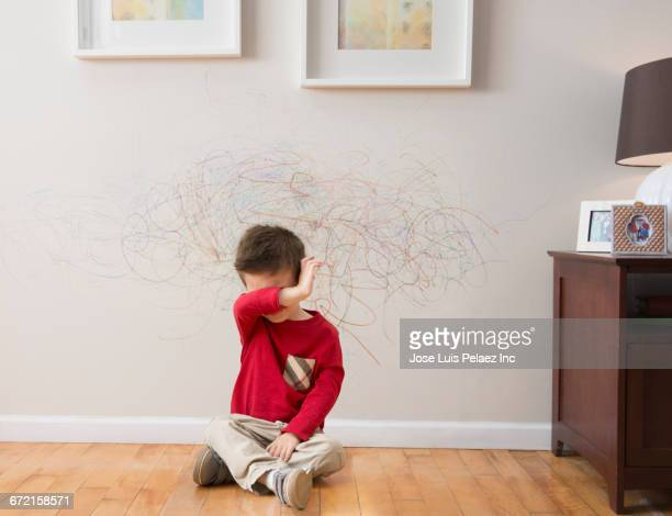 Mixed Race boy crying after drawing on wall with crayons