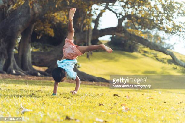mixed race boy doing hand stand. - nazar abbas photography stock pictures, royalty-free photos & images