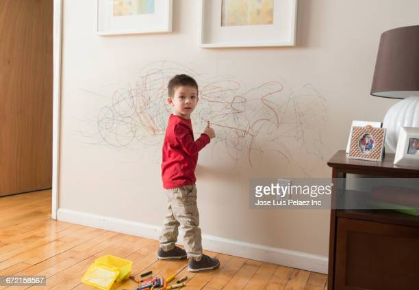 Mixed Race boy drawing on wall with crayons