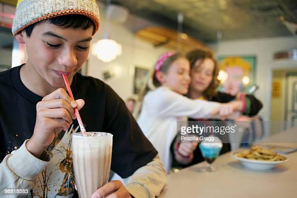 Mixed race boy drinking milkshake in cafe