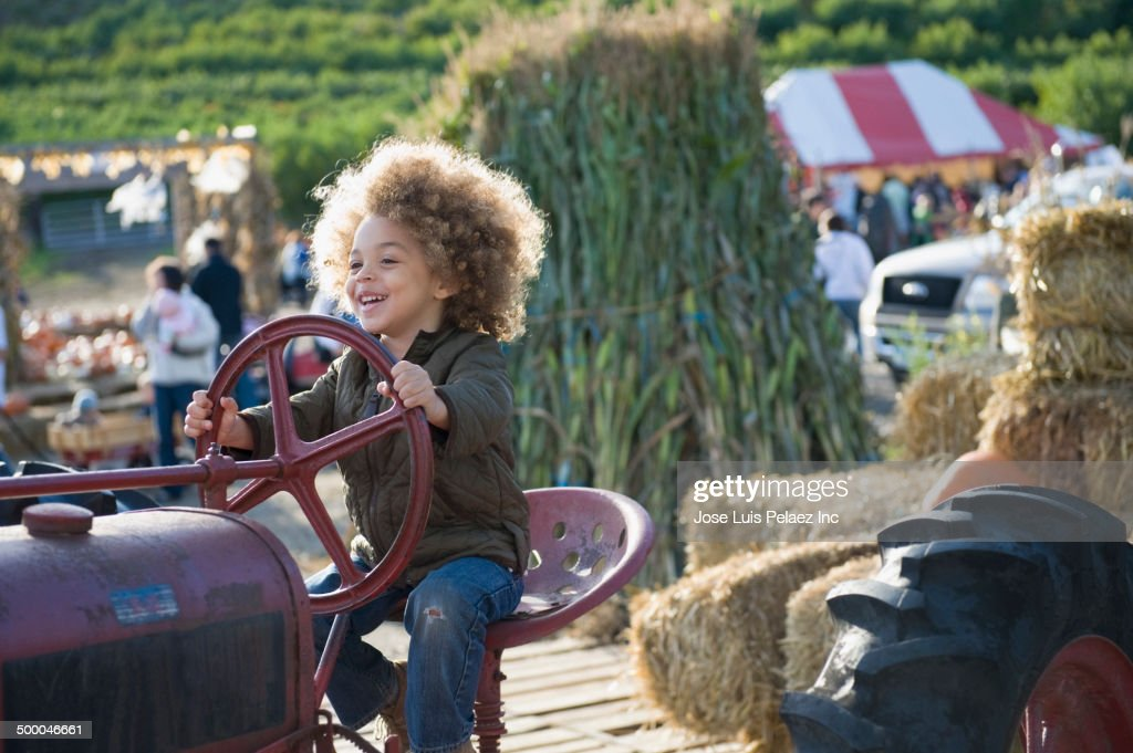 Mixed race boy driving tractor at farm : Stock Photo