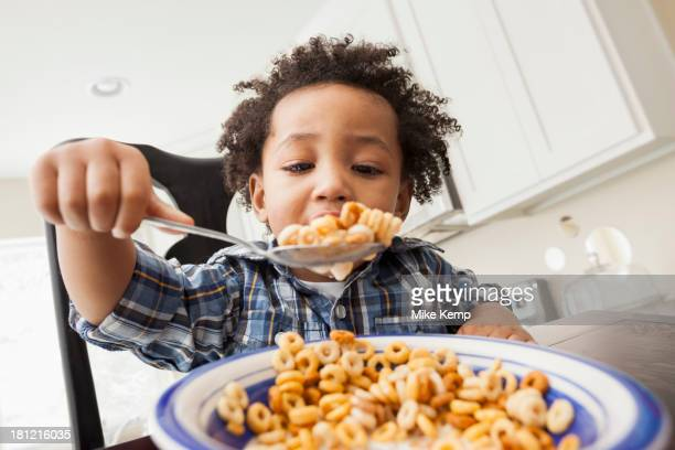 Mixed race boy eating at table