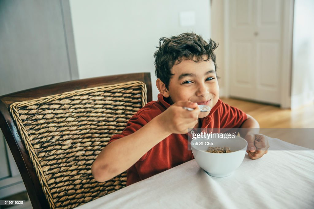 Mixed race boy eating cereal at table : Stock Photo