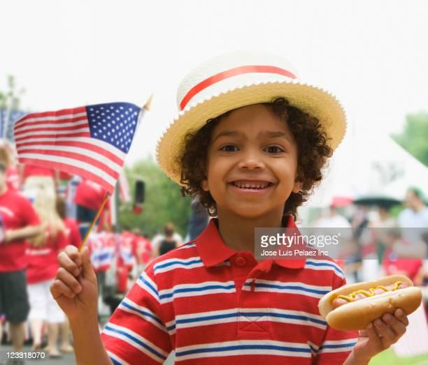 Mixed race boy eating hot dog at fourth of July celebration