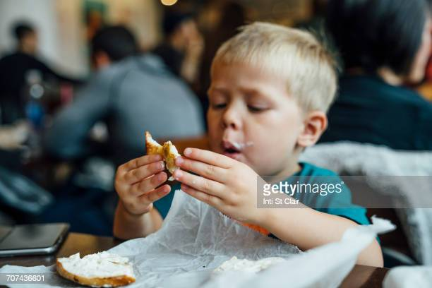 Mixed Race boy eating messy bagel in restaurant