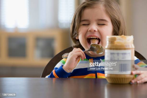 Mixed race boy eating peanut butter