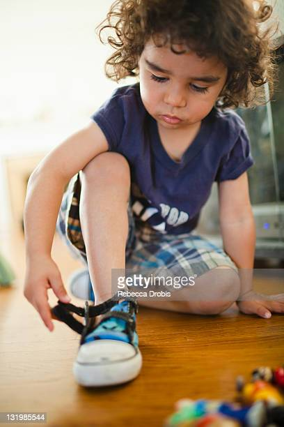 mixed race boy fastening shoes - nylon fastening tape stock photos and pictures