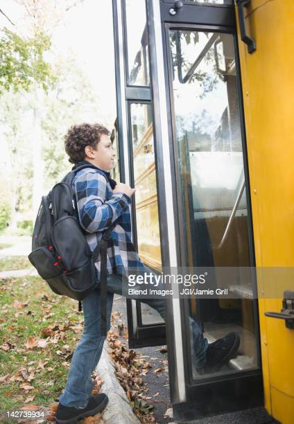 Mixed race boy getting onto school bus