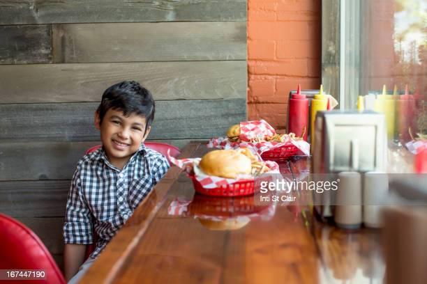 Mixed race boy having burgers in restaurant