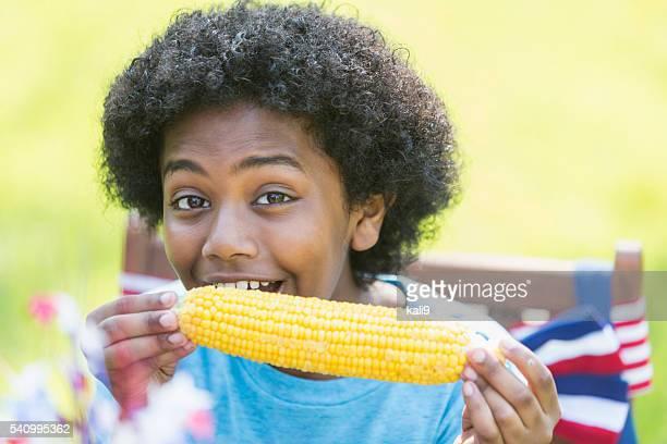 Mixed race boy having corn at 4th of July picnic