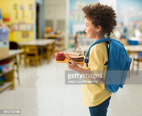 Mixed race boy having lunch at school