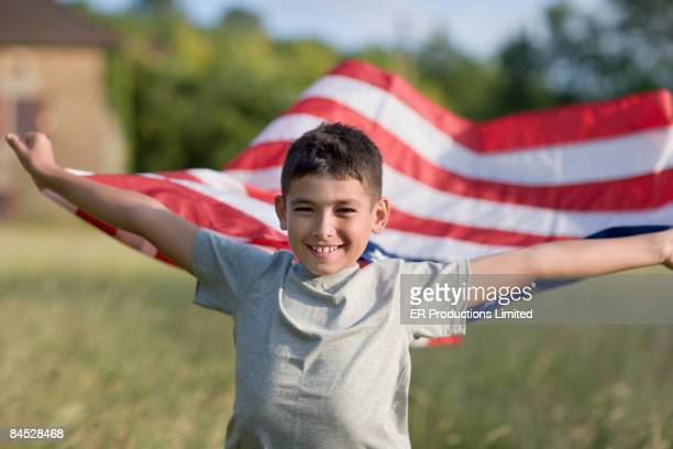 Mixed race boy holding American flag
