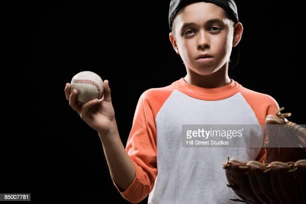 Mixed race boy holding baseball and baseball glove