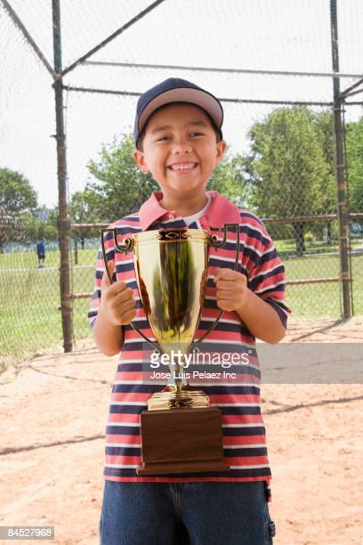 mixed race boy holding baseball trophy - trophy - fotografias e filmes do acervo
