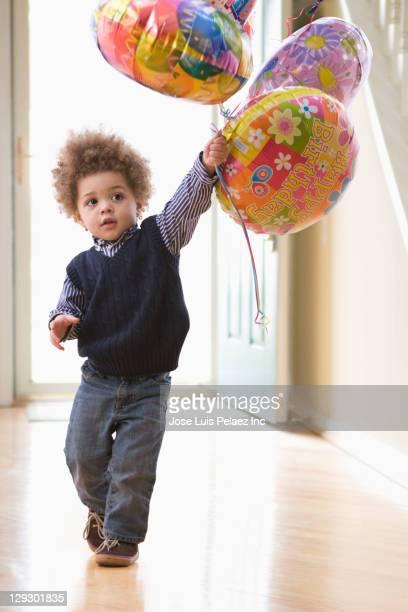 Mixed race boy holding birthday balloons