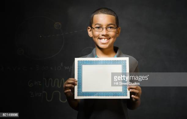 Mixed Race boy holding blank certificate