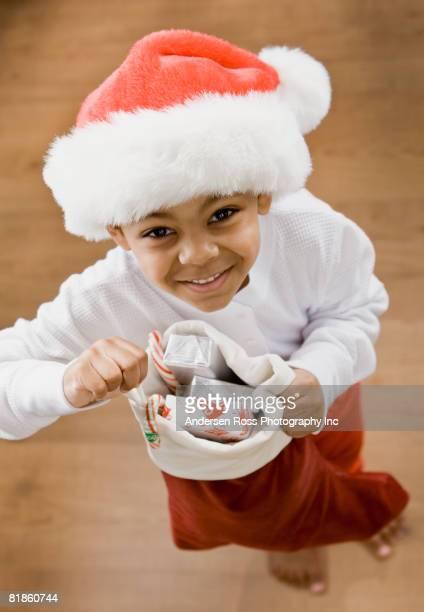 Mixed Race boy holding Christmas stocking