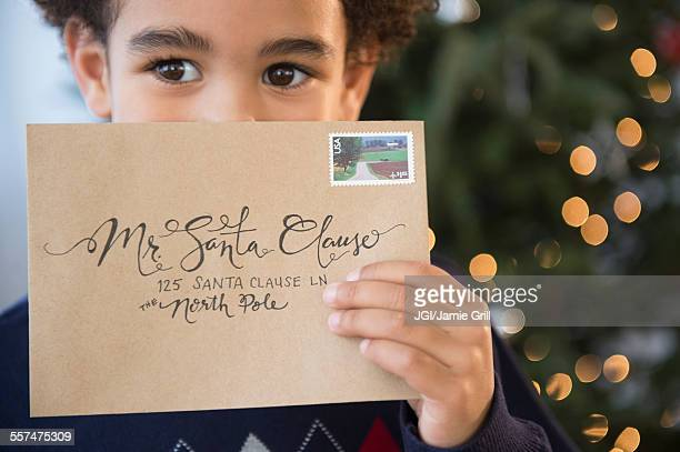 mixed race boy holding letter to santa for christmas - greeting card bildbanksfoton och bilder