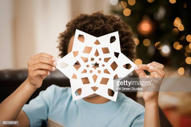 Mixed race boy holding paper snowflake