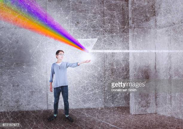 Mixed Race boy holding prism
