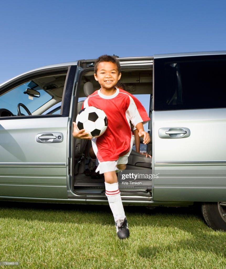 Mixed Race boy holding soccer ball : ストックフォト