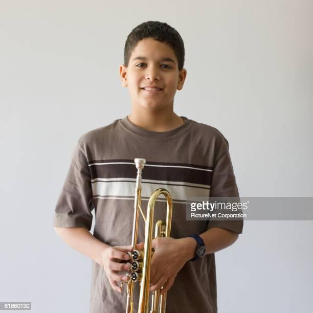 Mixed Race boy holding trumpet