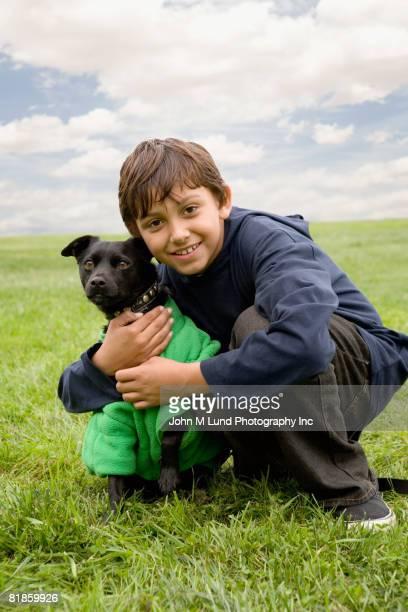Mixed Race boy hugging dog
